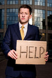 Businessman holding sign Help. Financial crisis. Unemployment. Young businessman holding sign Help outdoors Stock Image
