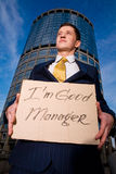 Businessman holding sign I am good Manager. Financial crisis. Unemployment. Smiling young businessman holding sign I am good Manager outdoors Stock Photos