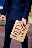 Businessman holding sign Need Job outdoors. Financial crisis. Unemployment. Businessman holding sign Need Job outdoors Stock Image