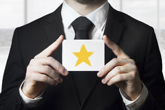 Businessman holding sign rating star gold. Businessman in black suit holding sign golden rating star royalty free stock photography