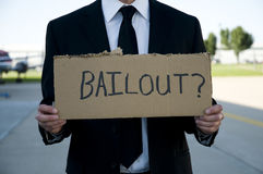 Businessman holding a sign that says bailout?. Businessman wearing a suit and tie holding a sign that says bailout Stock Image