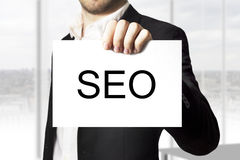 Businessman holding sign seo Stock Photos