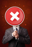 Businessman holding x sign. Smart businessman holding round red sign with a white cross Stock Image