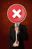 Businessman holding x sign. Smart businessman holding round red sign with a white cross Royalty Free Stock Photography