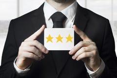 Businessman holding sign three golden rating stars. Businessman in black suit holding sign three golden rating stars royalty free stock photography