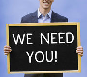 Businessman holding sign with words We Need You. Young businessman holding sign with words We Need You Stock Images