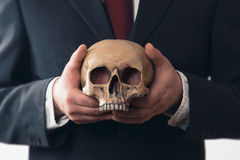 Businessman holding a Skull in his hands Stock Photography