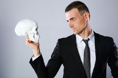Businessman holding skull Royalty Free Stock Photography