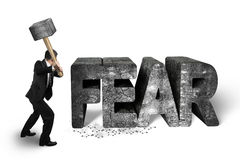 Businessman holding sledgehammer hitting fear concrete word isol Stock Images