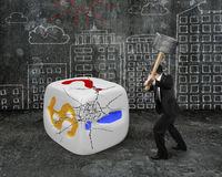 Businessman holding sledgehammer hitting large dice with buildin Stock Photos