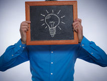 Businessman holding a small chalkboard with a lightbulb on it Stock Images
