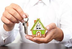 Businessman holding a small house and apartment keys in hand Royalty Free Stock Photography