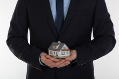 Businessman holding small house in hands. Insurance and security Royalty Free Stock Image