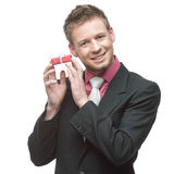 Businessman holding small red gift Royalty Free Stock Image
