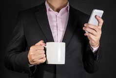 Businessman Holding Smart phone and Coffee mug on Black backgrou Royalty Free Stock Image
