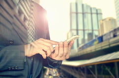 Businessman holding smart phone. Double exposure photo of panoramic city. View at sunright Stock Photos
