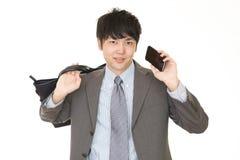 Smiling Asian businessman. Businessman holding a smart phone stock image