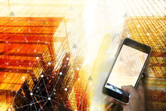 Businessman holding smart phone with wireless communication netw. Ork icon and cityscape background.E-commerce smart connection business. internet of things Stock Photo