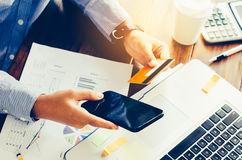 Businessman holding smart phone and work with laptop on the tabl. E and analyzing investment chart working in office. Business work concept Royalty Free Stock Images