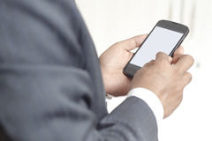 Businessman holding smartphone with blank screen Royalty Free Stock Photo