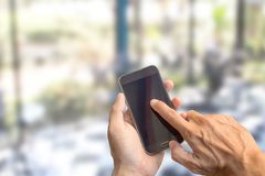Businessman holding smartphone with blurred background. Blank space for graphic display montage Stock Images