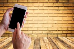 Businessman holding smartphone with blurred brick wall and wood. Table background. Blank space for graphic display montage and your product Stock Photography