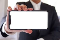 Businessman holding smartphone forward empty white screen for your text or picture. royalty free stock images