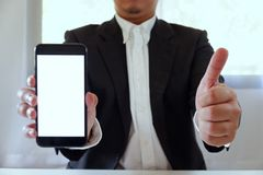 Businessman holding smartphone forward empty white screen for your text or picture stock photos