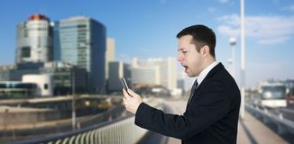 Businessman Holding Smartphone in Hand And Feeling Angry With Business City and Corporate Buildings In Background royalty free stock photos