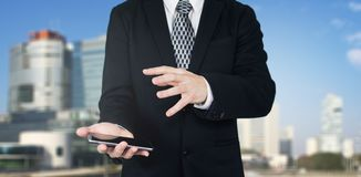 Businessman Holding Smartphone in Hand With Hand Gesture Over The Phones Screen With Business City and Corporate Buildings In. The Background stock photo