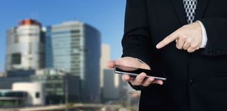 Businessman Holding Smartphone in Hand And Pointing Index Finger At The Phones Screen With Business City and Corporate Buildings. In The Background stock image
