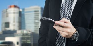Businessman Holding Smartphone in Hand And Typing a Message With Business City and Corporate Buildings In Background stock photography