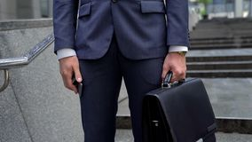 Businessman holding smartphone and leather briefcase, successful investment stock photography