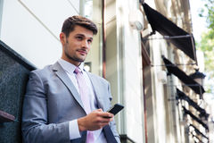 Businessman holding smartphone outdoors Royalty Free Stock Images