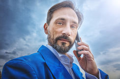 Businessman holding a smartphone, portrait, day, outdoor. Middle-aged businessman talking on the phone, and looking in camera. Man in blue jacket, on the Royalty Free Stock Photography