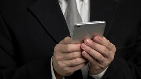 Businessman holding smartphone and typing. Back view smartphone with fingerprint stock footage