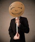Businessman holding a smiley face board Stock Photos