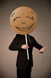 Businessman holding a smiley face board Stock Photography