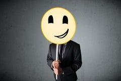 Businessman holding a smiley face emoticon Stock Photos