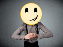 Businessman holding a smiley face emoticon Royalty Free Stock Image