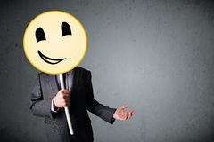 Businessman holding a smiley face emoticon Royalty Free Stock Photography