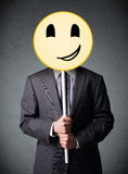 Businessman holding a smiley face emoticon Stock Photos