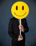 Businessman holding a smiley face emoticon Royalty Free Stock Photos