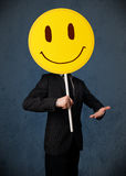 Businessman holding a smiley face emoticon Stock Images