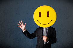 Businessman holding a smiley face emoticon. Businessman holding a yellow smiley face emoticon in front of his head Royalty Free Stock Photos