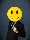 Businessman holding a smiley face emoticon Stock Photography