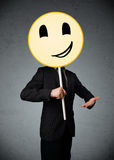 Businessman holding a smiley face emoticon Stock Image