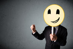 Businessman holding a smiley face emoticon Royalty Free Stock Photo
