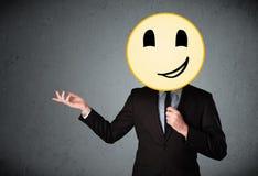 Businessman holding a smiley face emoticon Royalty Free Stock Photos