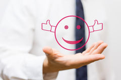 Businessman holding smiley with thumbs up Royalty Free Stock Image